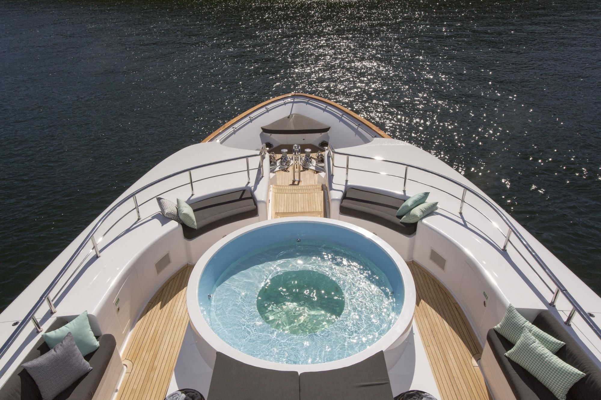 Watch race day preparations from the hot tub on the deck of a superyacht.