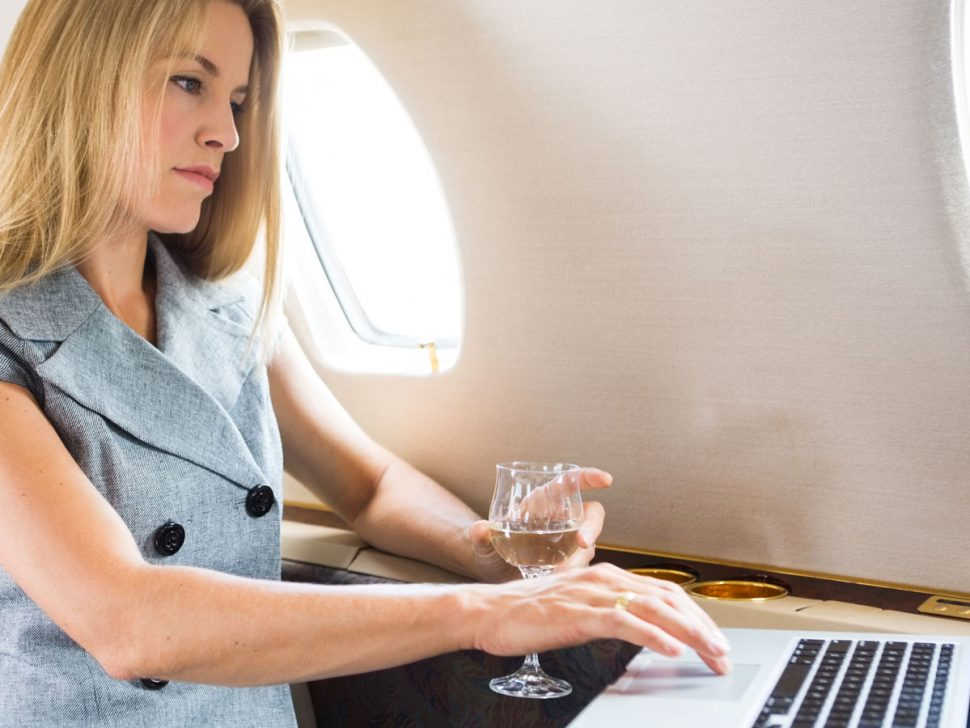 Woman On Private Jet Writes On Laptop, Holding Glass Of Wine