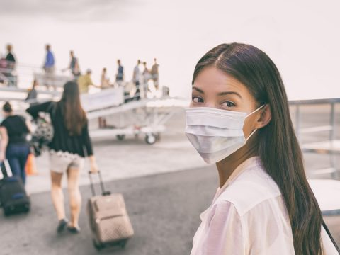 Woman With Face Mask Boards Plane