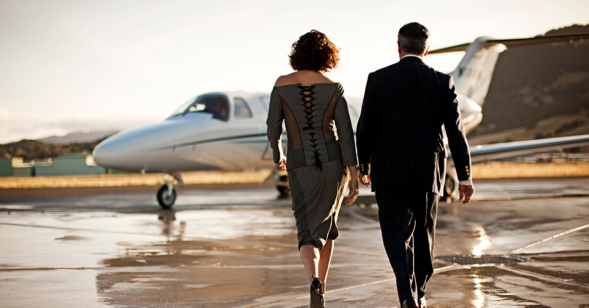 Well Dressed Man And Woman Approach Private Jet