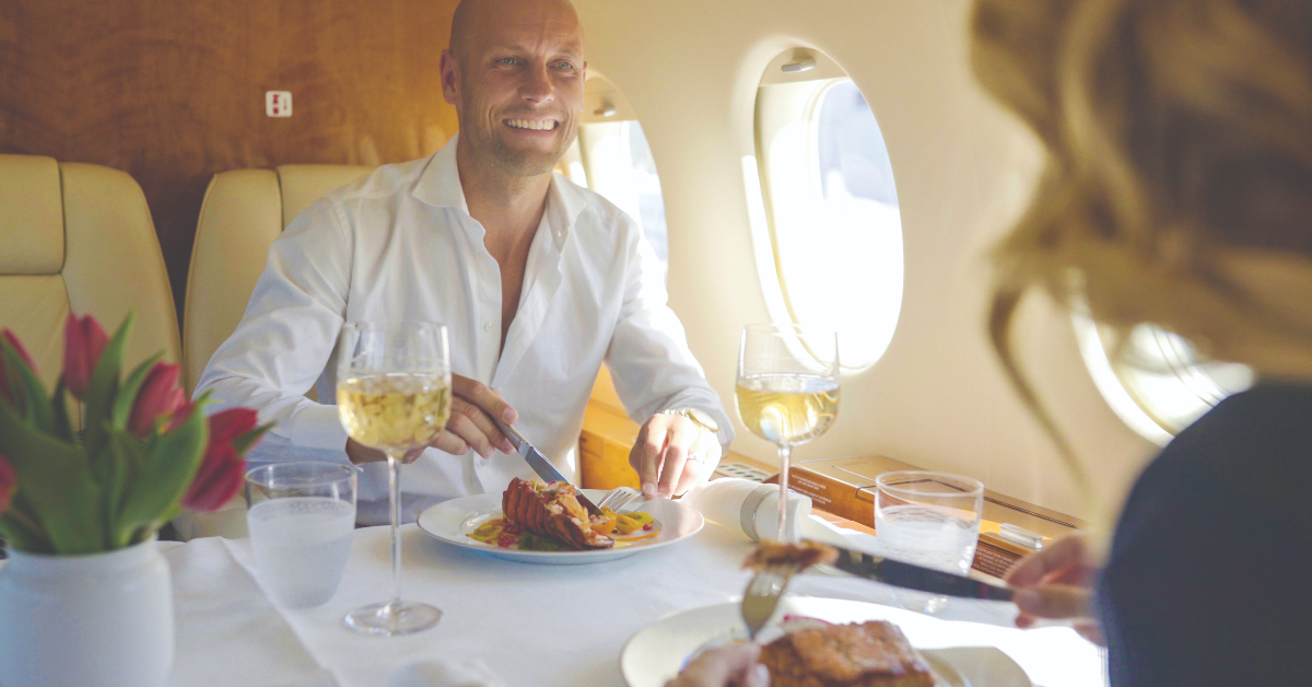 """alt=""""Two people enjoying a meal in the Dassault Falcon 900"""""""